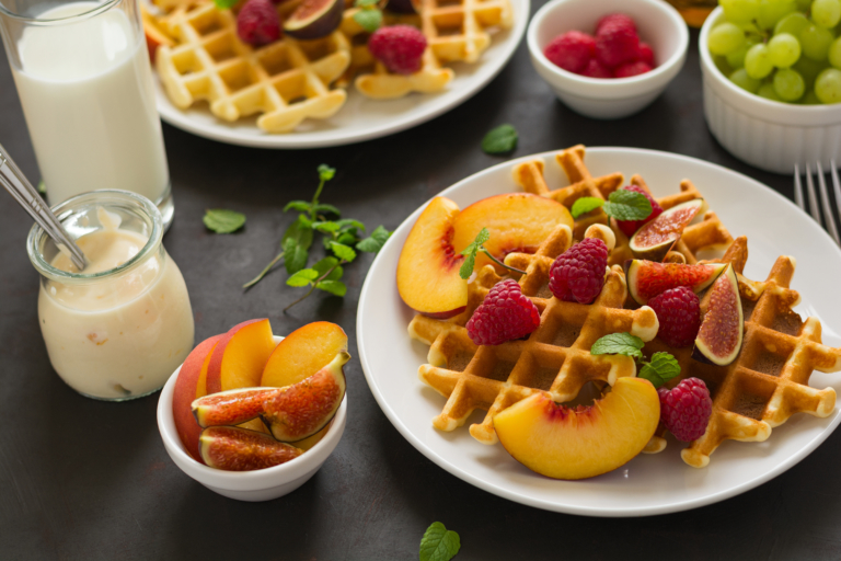 Homemade Belgian waffles with peach, raspberry, fig and honey on brown wooden background. Selective focus